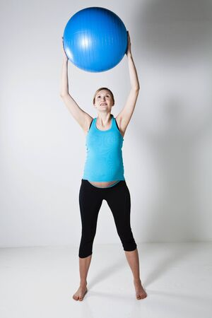 Pregnant woman holding a blue fitness ball above head Stock Photo - 12970176
