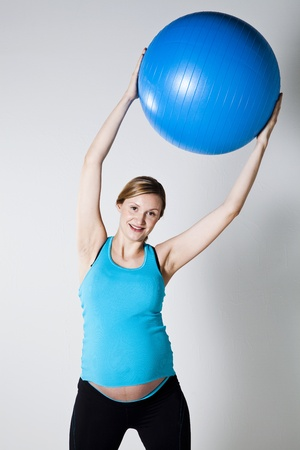 Pregnant woman exercising with a blue fitness ball held above head