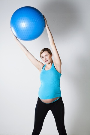 Pregnant woman exercising with a blue fitness ball held above head Stock Photo - 12970240