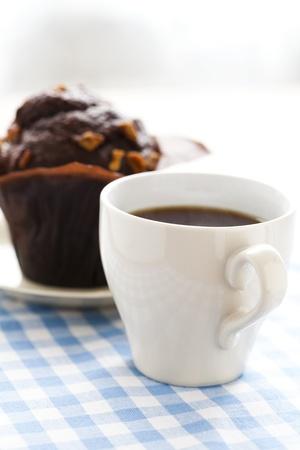 magdalenas: Primer plano de una taza de caf� negro y un bollo de chocolate. Foto de archivo