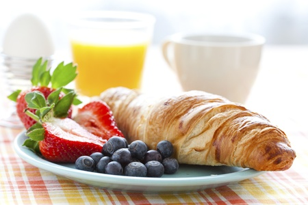 breakfast eggs: Croissant, fresh strawberries and blueberries, coffee, orange juice and an egg for healthy breakfast