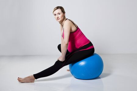 hamstring: Pregnant woman performing a leg stretching exercise for the hamstring muscles sitting on a fitness ball