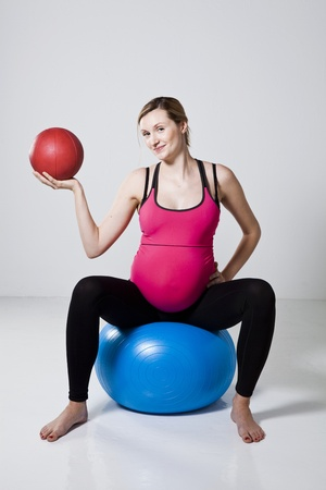 Pregnant woman exercising with a red exercise ball while sitting on a blue fitness ball Stock Photo - 13314174