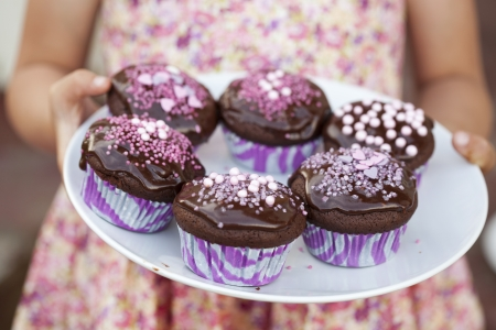 Close-up of hands holding a plate of delicious chocolate cupcakes with chocolate icing and sprinkles photo