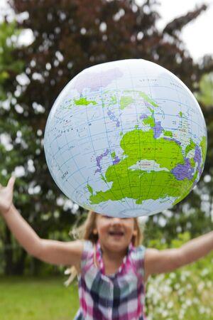 Little girl throwing an earth globe high in the air. Motion blur. photo