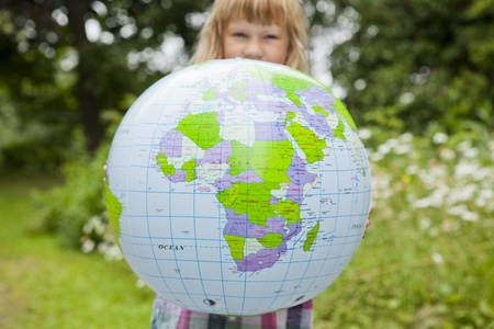 Little girl holding a colorful earth globe outdoors Stock Photo - 15036763