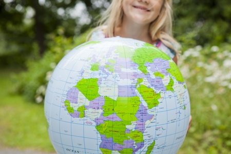Little girl holding a colorful earth globe outdoors photo