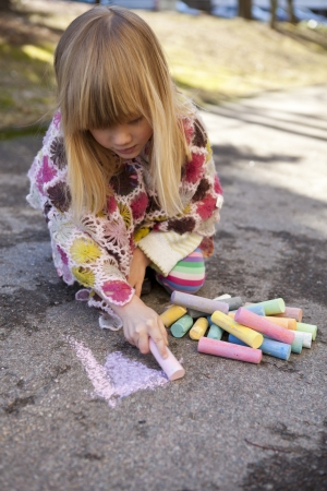 Cute little girl drawing with chalk outdoors photo