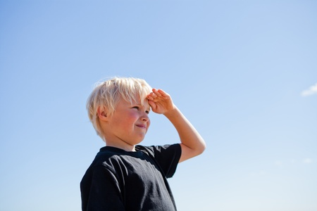 hand on forehead: Boy outdoors looking ahead with hand on forehead