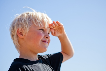 Boy outdoors looking ahead with hand on forehead