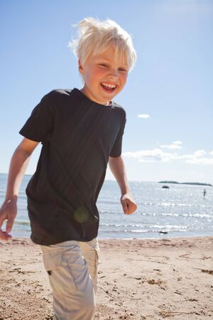 Boy on the beach on a beautiful sunny summer day Stock Photo