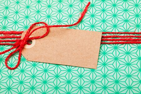 Close up of simple gift in green wrapping with red string and brown cardboard tag photo