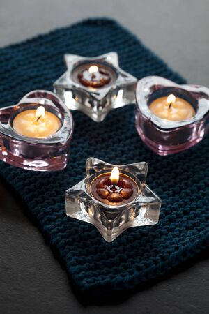 Close up of candles in star and heart shaped glass holders on a blue mat photo