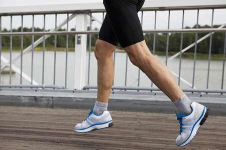 stride: Legs of an athletic adult male runner while in mid stride going over bridge