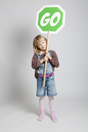 Studio portrait of young girl holding green go sign photo