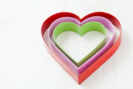 Colorful nested metal heart shapes on white background