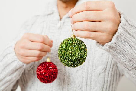 Closeup of red and green Christmas baubles hanging from fingers photo