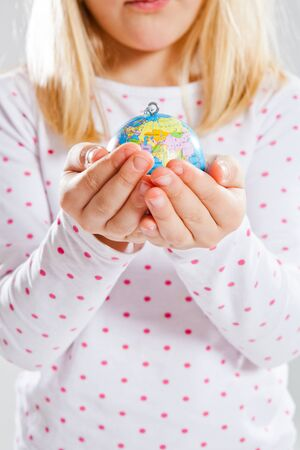 Studio portrait of young girl holding world globe in hands photo