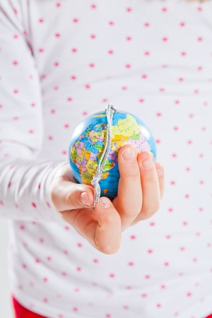 Studio portrait of young girl holding world globe in hand Stock Photo - 17037079