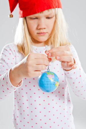 Studio portrait of young girl with red Christmas elf hat holding world globe in hands photo