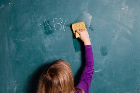Young girl wiping letters written in chalk from chalkboard with wet sponge Stock Photo