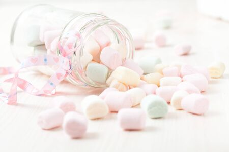 Colorful marshmallows in glass jar with ribbon on light background