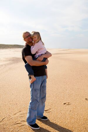 Father holding young daughter in arms at beach while on vacation in Portugal photo