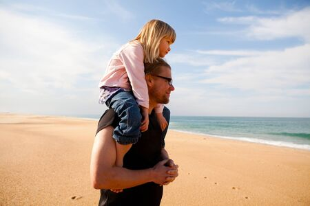 padre e hija: Padre que lleva a cuestas en los hombros de la joven hija en la playa
