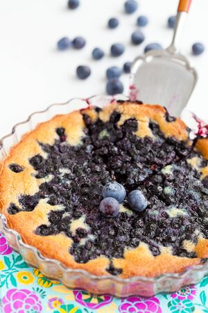 serving utensil: Closeup of delicious blueberry pie in glass dish with serving utensil