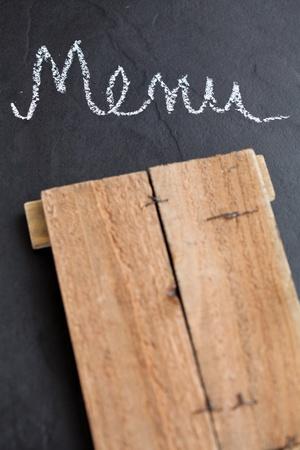 Closeup of wooden board and word menu written in chalk on dark background photo
