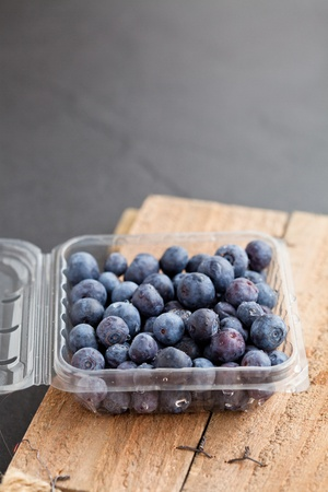 Closeup of fresh blueberries in plastic container resting on wooden serving surface photo