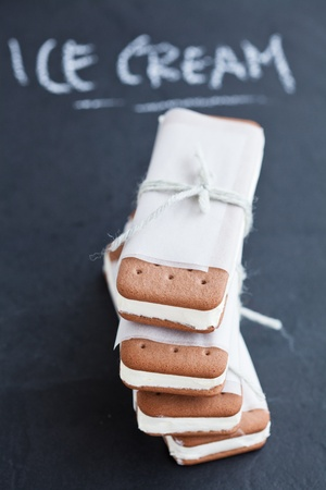 Closeup of stack of vanilla ice cream biscuits wrapped in white paper with string and bow and word ice cream written in chalk in background photo