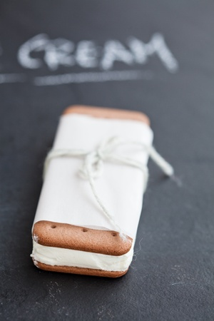 Closeup of stack of vanilla ice cream biscuits wrapped in white paper with string and bow and word cream written in chalk in background photo