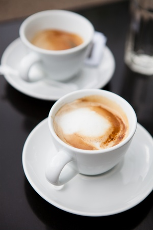 coffees: Closeup of two milk based coffees in white cups on cafe table Stock Photo
