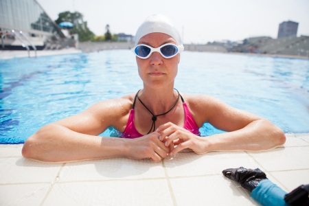 Female freediver wearing goggles and resting at edge of outdoor swimming pool