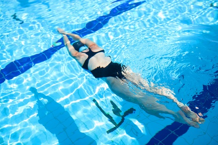 Female freediver diving underwater in outdoor swimming pool