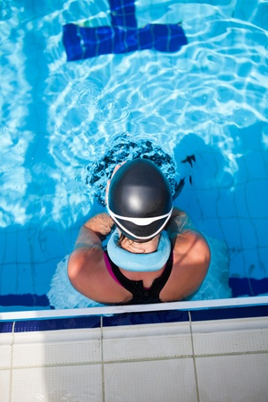 freediver: Female freediver with neck weight and monofin at edge of outdoor swimming pool Stock Photo