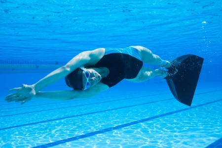 Female freediver with monofin swimming underwater in swimming pool in sideways position Stock Photo