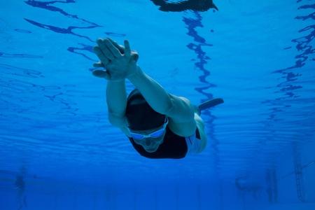 Vrouw freedivermeisje met monofin onderwater zwemmen in zwembad Stockfoto