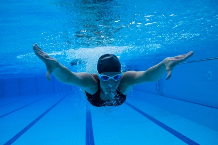 Female swimmer diving underwater in swimming pool photo