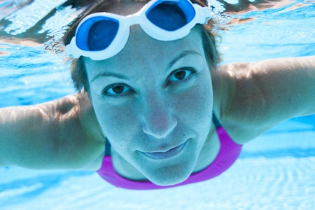 Closeup of face of female swimmer underwater in swimming pool with eyes open Stock Photo