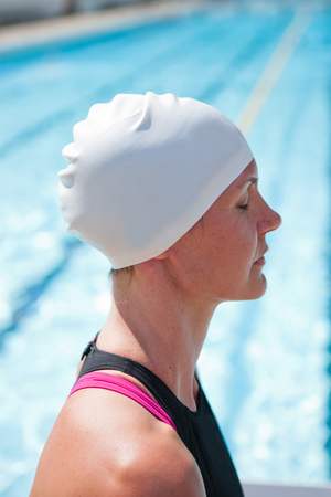 swimming cap: Female swimmer beside swimming pool concentrating with eyes closed
