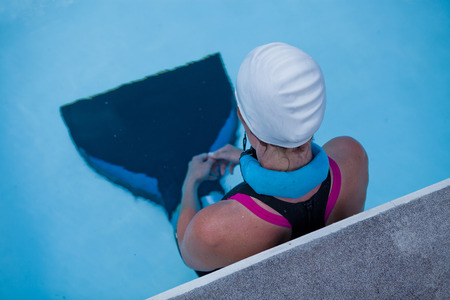 Female freediver with monofin concentrating and preparing at edge swimming pool