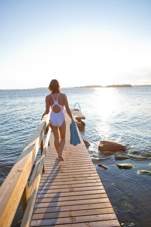 nordic country: Attractive woman in white bathing suit walking on wooden pier in nordic country during summer Stock Photo