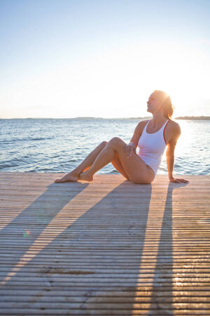 nordic country: Attractive woman in white bathing suit sitting on wooden pier in nordic country during summer