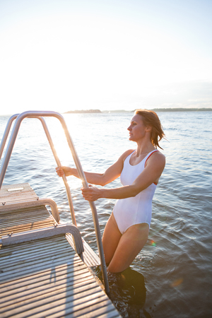 nordic country: Attractive woman in white bathing suit climbing up ladder on to wooden pier in nordic country during summer