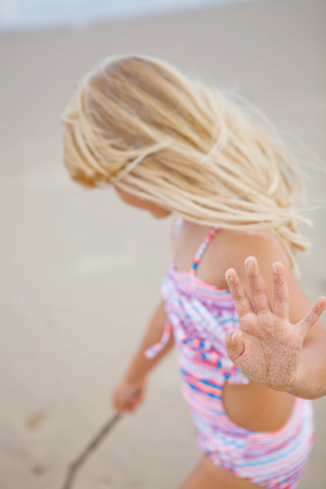 Focus on sand covered hand of young cute girl playing with stick at the beach photo