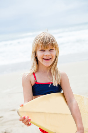 Happy smiling cute young girl with surfboard on beach with ocean in background photo