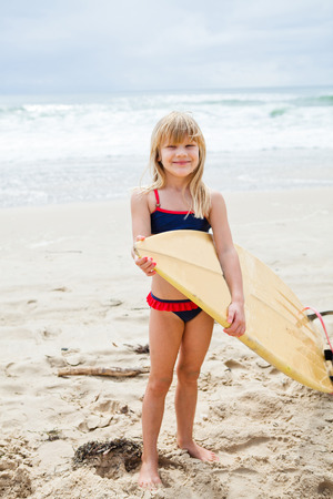 Happy smiling cute young girl holding surfboard on beach with ocean in background photo