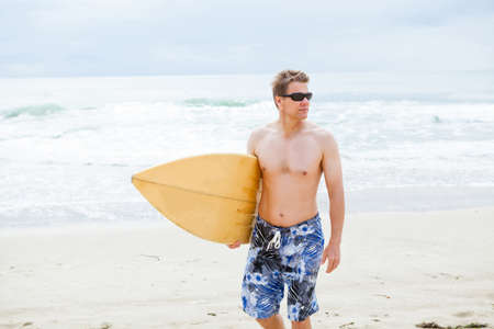 Serious looking male surfer walking on beach while carrying surfboard